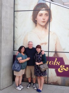 Photo of Dena, Brian, and Natalie DeMint in front of Angels and Tomboys poster.